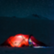 Torkjel in the tent below a starlit sky and the Elbrus summit. Photo: Andreas Ebbesen