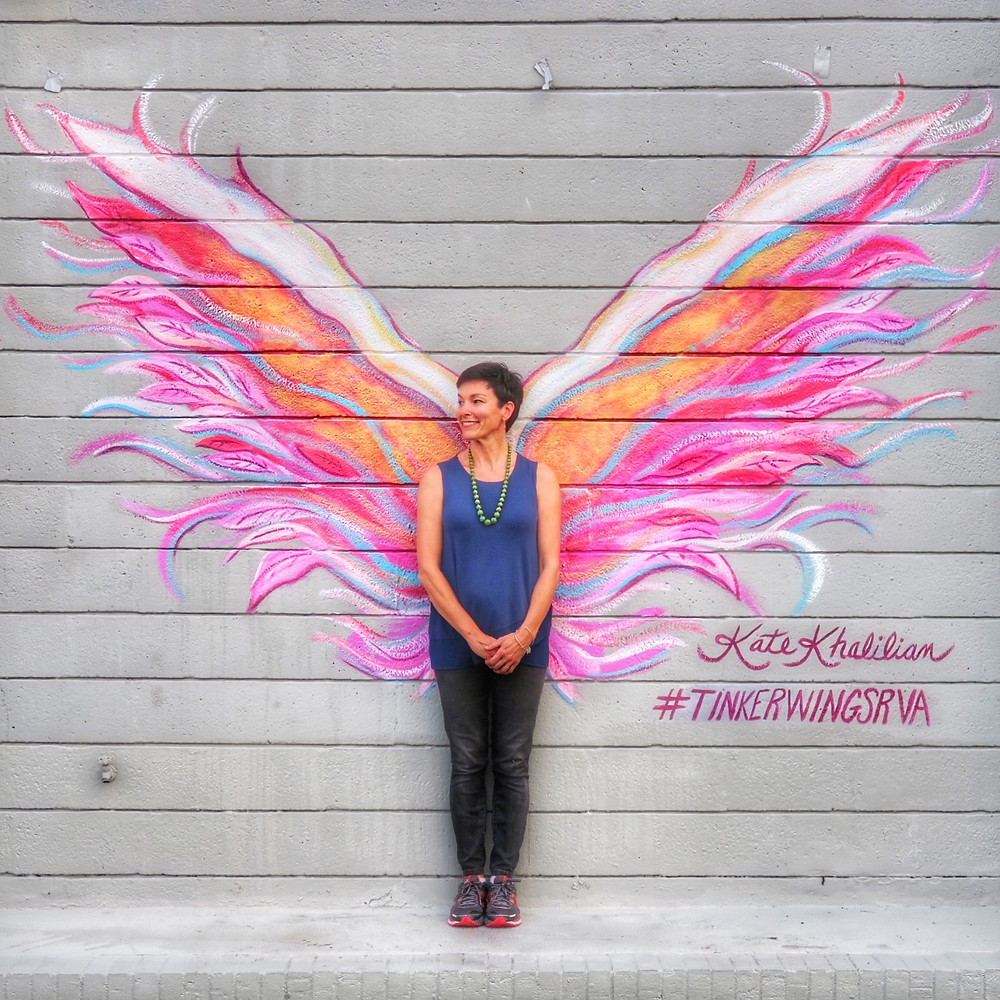 Tinker's decorative artist, Kate Khalilian, stands in front of her angel wing wall mural.