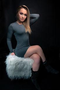 Breanna Leblanc (Brefit) assise sur un poufe en fourure et avec une robe grise