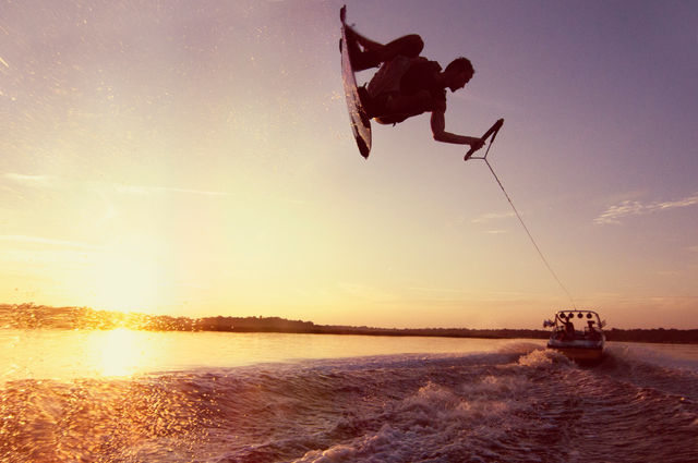 wakeboarder at sunset behind boat