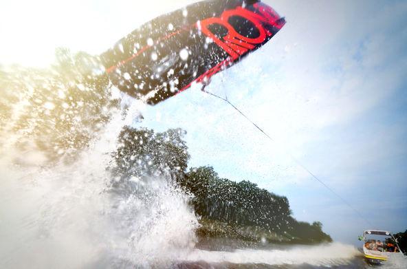 Ronix wakeboard almost hits camera man behind boat splash advertisement
