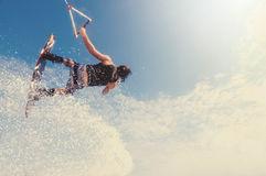 Ronix Body Glove Hyperlite wakeboarder in air with spray