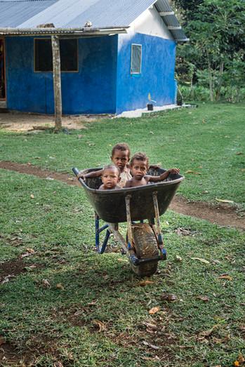 Children in a wheelbarrow, Santo Island, Vanuatu, 2019.