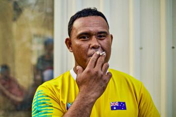 A young Tongan man smoking, Tasmania, Australia, 2018.