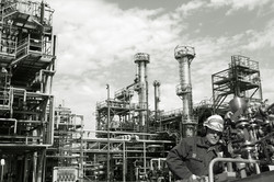 oil-worker, engineer, with pipelines machinery, large refinery in background, duplex toning concept