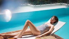 Woman sunbathing on lounge chair at luxury poolside