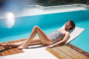 Donna-sole-on-lounge-sedia-a-lusso-a bordo piscina