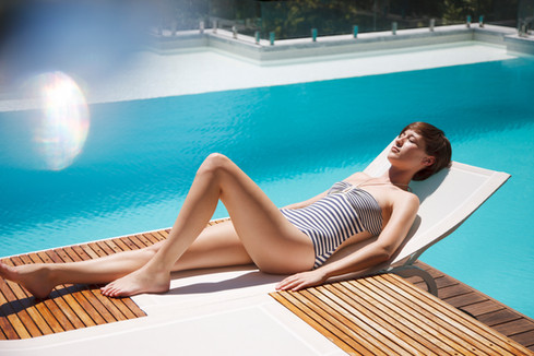 Woman-sunbathing-on-lounge-chair-at-luxury-poolside