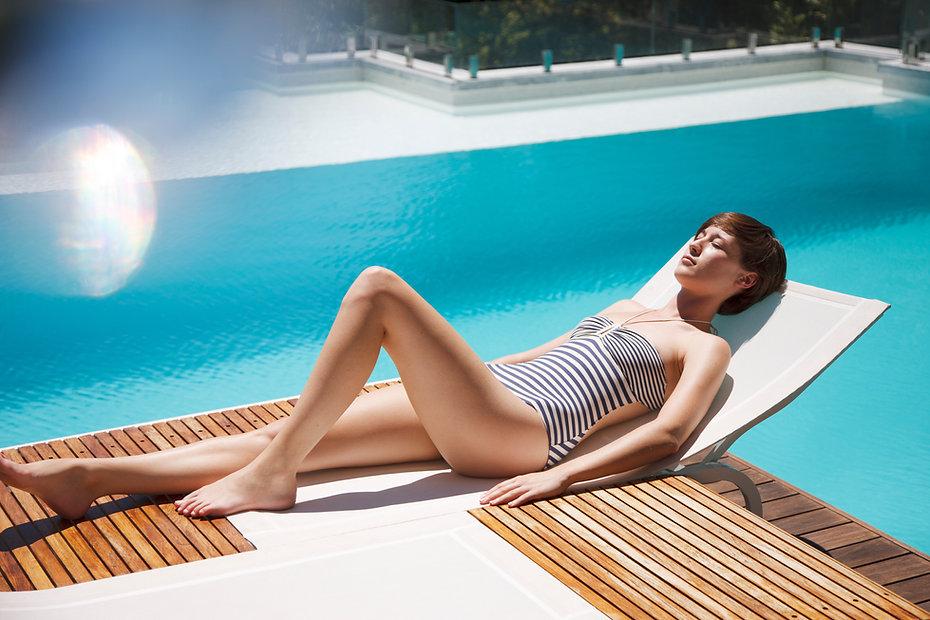 Woman sunbathing on lounge chair at luxu