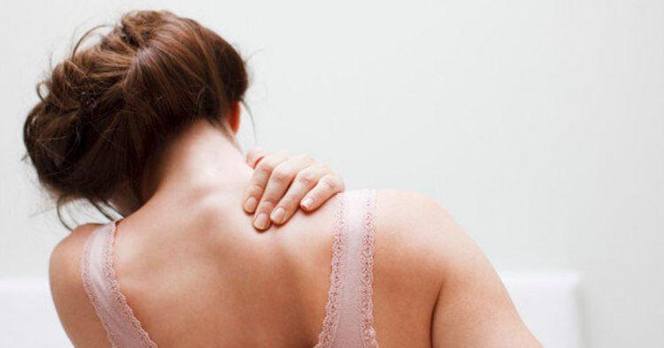 woman rubbing achy shoulder