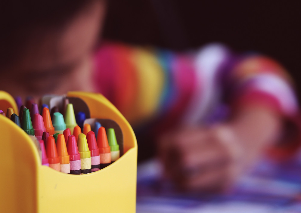 Preparing for back to school. Girl sitting at school table coloring. A letter to the teacher of my healthy kid. Special needs sibling.