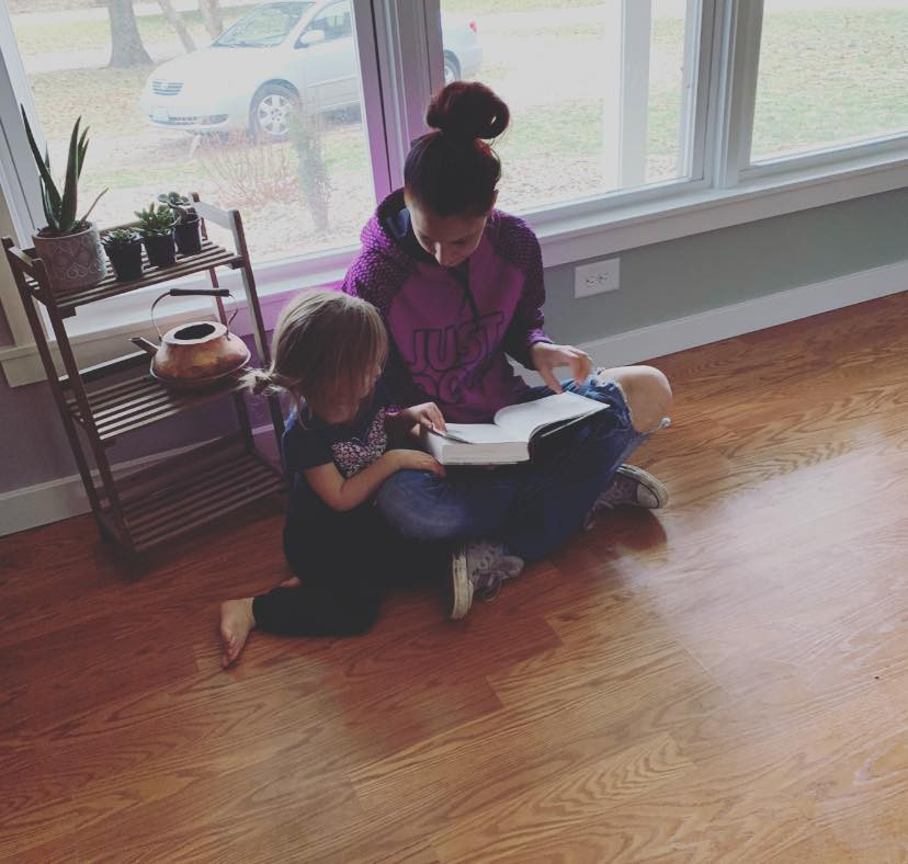 Mom sitting with special needs child, reading Bible. Maybe God isn't good.