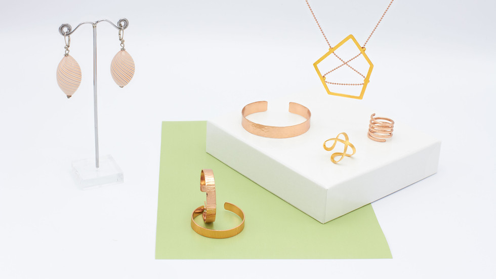Jewelery from the Sélection Actuelle with jewelery from the spring collection with a creole, a bracelet and ring made of rose gold, a ring made of brushed gold, a gold necklace with rose gold and oval earrings made of colored glass