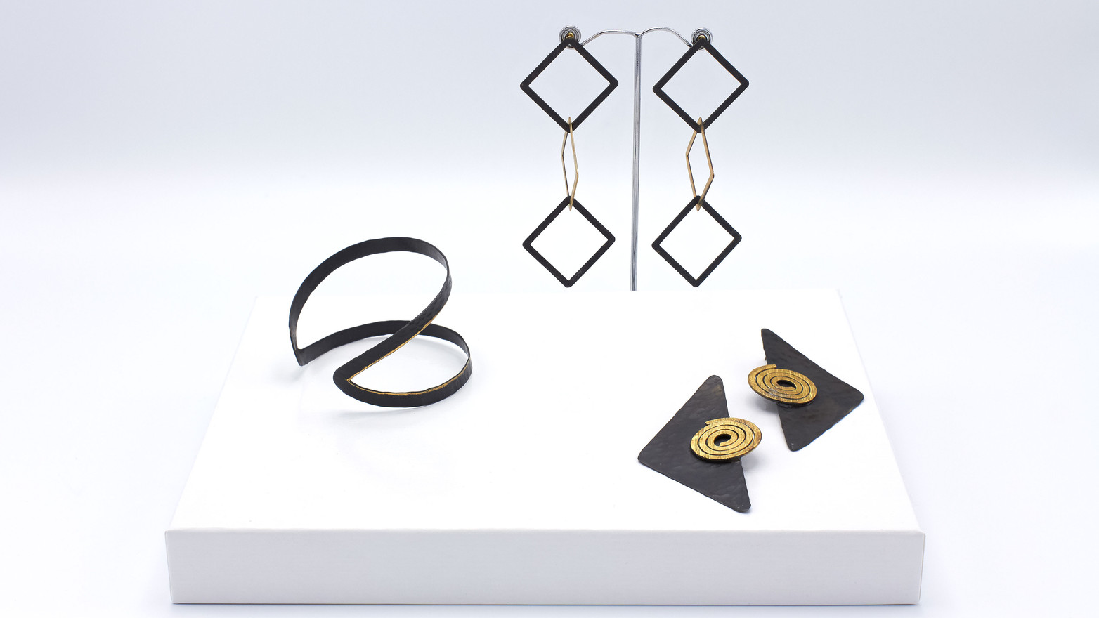 Jewelery from the Sélection Actuelle with jewelery from the spring collection with a bracelet, and two earrings made of dark bronze with gold-plated parts, in particular two gold-plated spirals