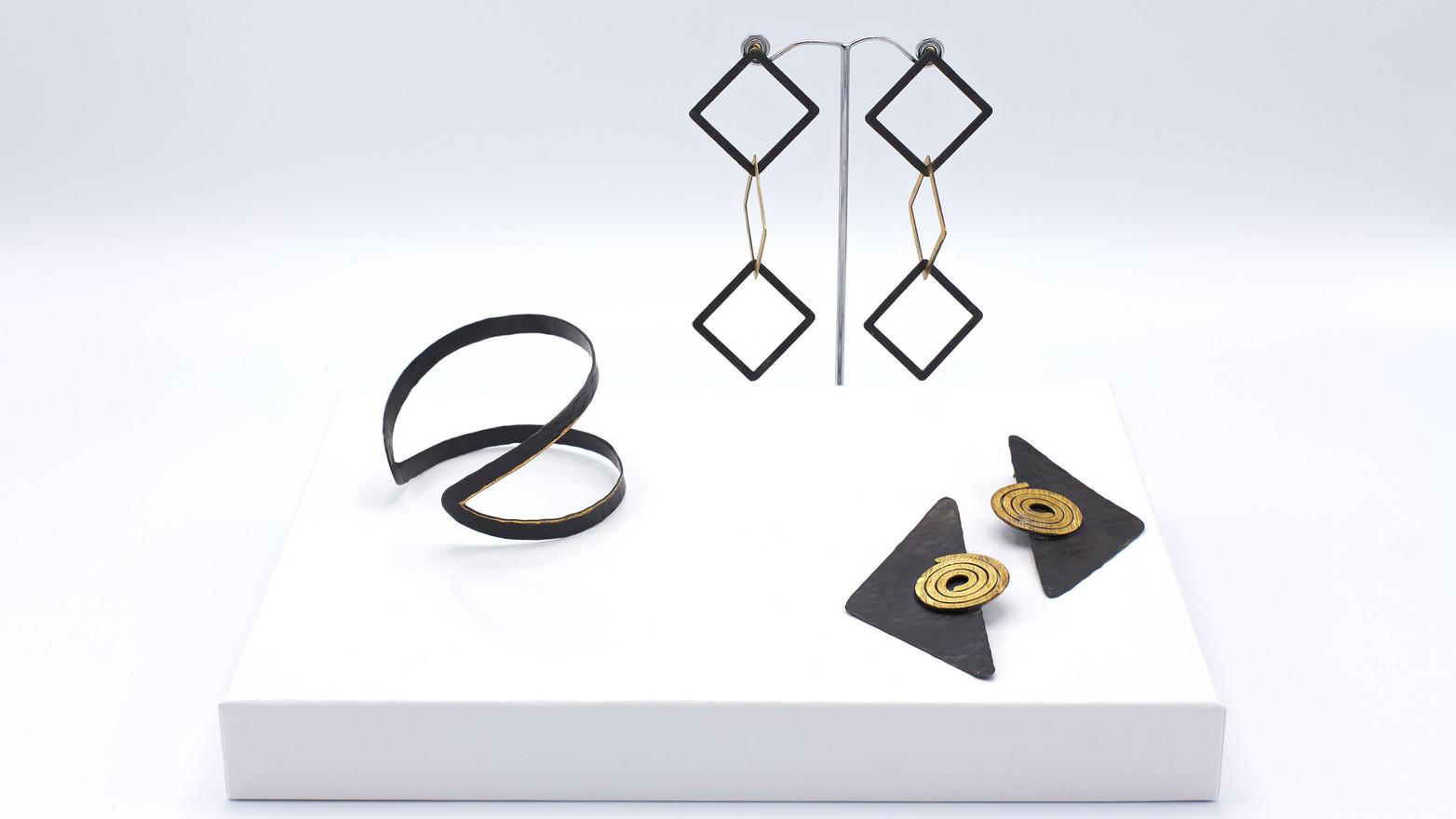 Schmuckstücke aus der Sélection Actuelle mit Schmuck aus der Frühlings Kollektion mit einem Armreif, und zwei Ohrringen aus dunkler Bronze mit vergoldeten Teilen, insbesondere zweier vergoldeter Spiralen