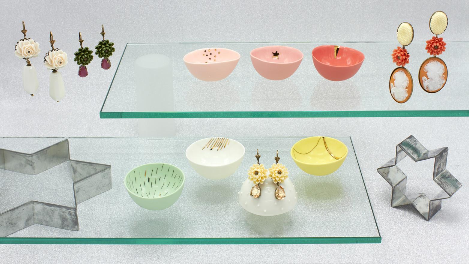 Schmuckstücke aus der Sélection Actuelle mit buntem Schmuck aus der Winter Kollektion mit Ohrringen verziert mit Blumenornamenten und Halbedelsteinen sowie handgefertigter bunter Keramikschalen der Künstlerin Maria Sabrina