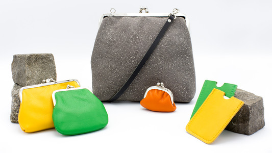 Schmuckstücke aus der Sélection Actuelle mit Accessoires aus der Herbst Kollektion mit einer grauen mit weissen Punkten gemusterten Handtasche, ledernen Münzportemonnaies und Kreditkartenhalter aus Leder