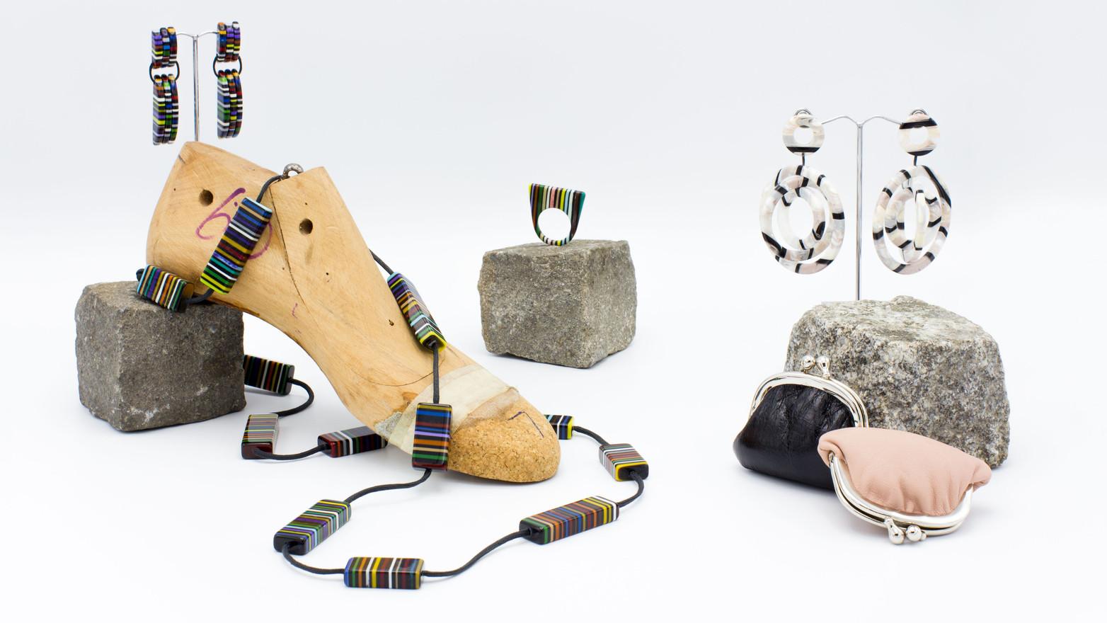 Schmuckstücke aus der Sélection Actuelle mit bunte, Schmuck aus der Herbst Kollektion mit einer Halskette, einem flachen Ring, Ohrringen aus buntem Kunststoff sowie ledernen Münzportemonnaies