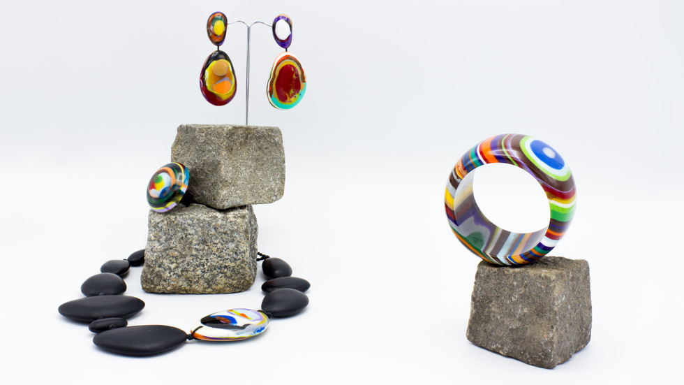 Jewelery from the Actuelle Sélection with jewelery from the autumn collection with two granite paving stones stacked on top of one another with colorful plastic costume jewelery. At the top hang two pebble-like colorful earrings, underneath a colorful round ring and at the bottom around the two granite stones is a necklace made of large pebble-like elements, all of which are black except for one colored one. To the right of this is a colorful bracelet on a granite stone