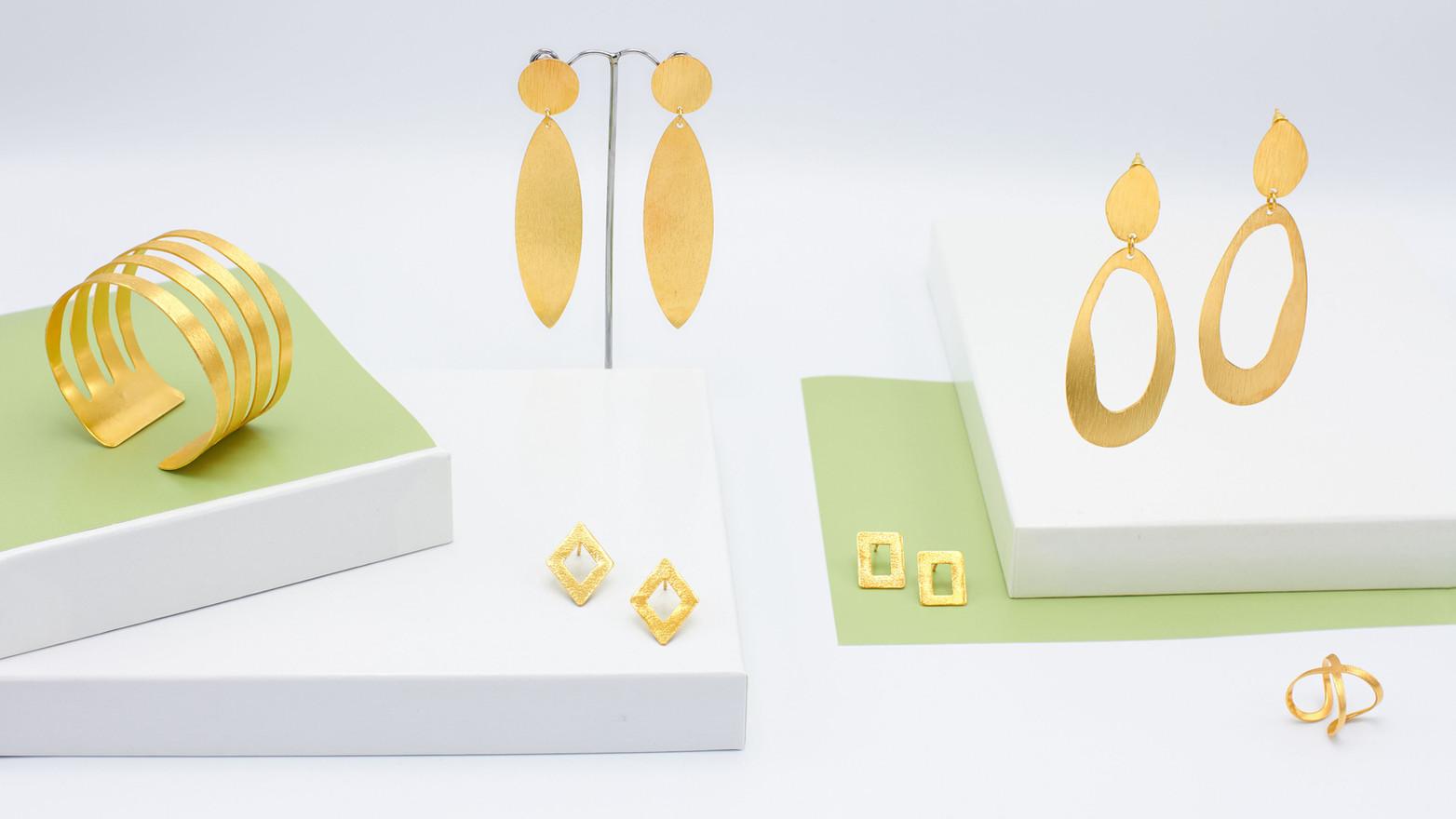 Schmuckstücke aus der Sélection Actuelle mit Goldschmuck aus der Frühlings Kollektion mit einem Armreif, einem Ring und zwei ovalen Ohrringen aus gebürstetem Gold, wie auch einem Paar rechteckiger und karoförmiger Goldohrringe