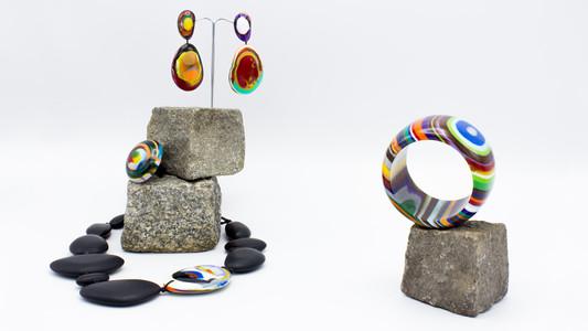 Schmuckstücke aus der Sélection Actuelle mit Schmuck aus der Herbst Kollektion mit zwei aufeinander gestapelten Granitpflastersteinen mit buntem Modeschmuck aus Kunststoff. Zuoberst hängen zwei kieselsteinähnliche bunte Ohrringe, darunter en bunter runder Ring und zuunterst liegt um die beiden Granitsteine herum eine Halskette aus grossen kieselsteinähnlichen Elementen, welche bis auf ein buntes alle schwarz sind. Rechts davon befindet sich ein bunter Armreif auf einem Granitstein