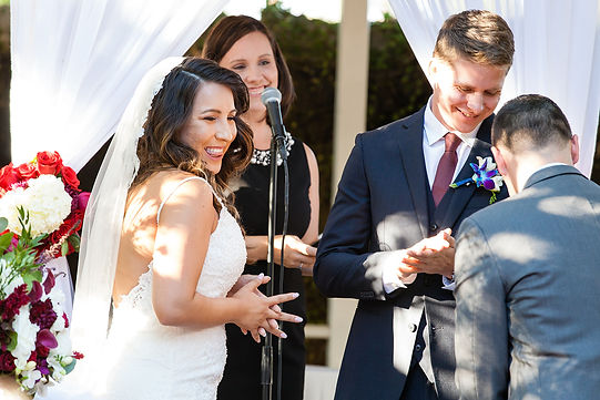 A bride giggles in anticipation as the groom retrieves the wedding ring during a wedding ceremony by Officiant Amber