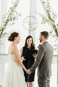 A bride and groom smile at one another during their wedding vows with Officiant Amber in an intimate wedding ceremony.