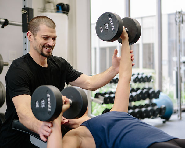 Personal Trainer working with a client doing a private training session. The exercise she is doing is Alternating Dumbbell Bench Press.