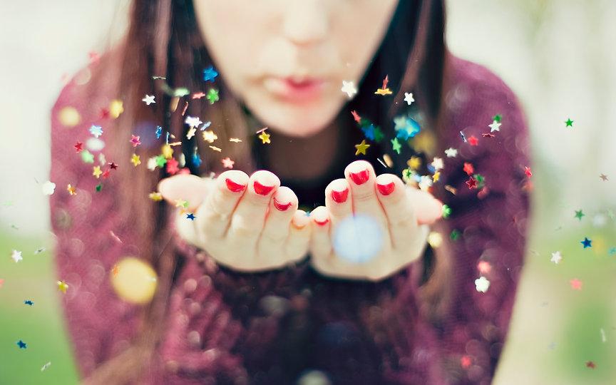 woman-blowing-confetti-towards-camera