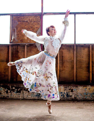 female ballett dancer in a bubble wrap scirt and flower top doing a dance pose in a derelict building