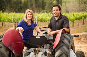 This is a photo of the owners, Noelle & Roberto standing next to a red tractor with their estate vineyard in the background.