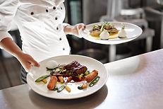 Serveur avec 2 assiettes de plats principaux