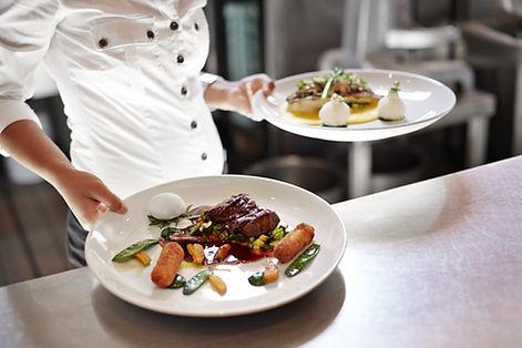 Serveur dans un restaurant avec deux assiettes à la main