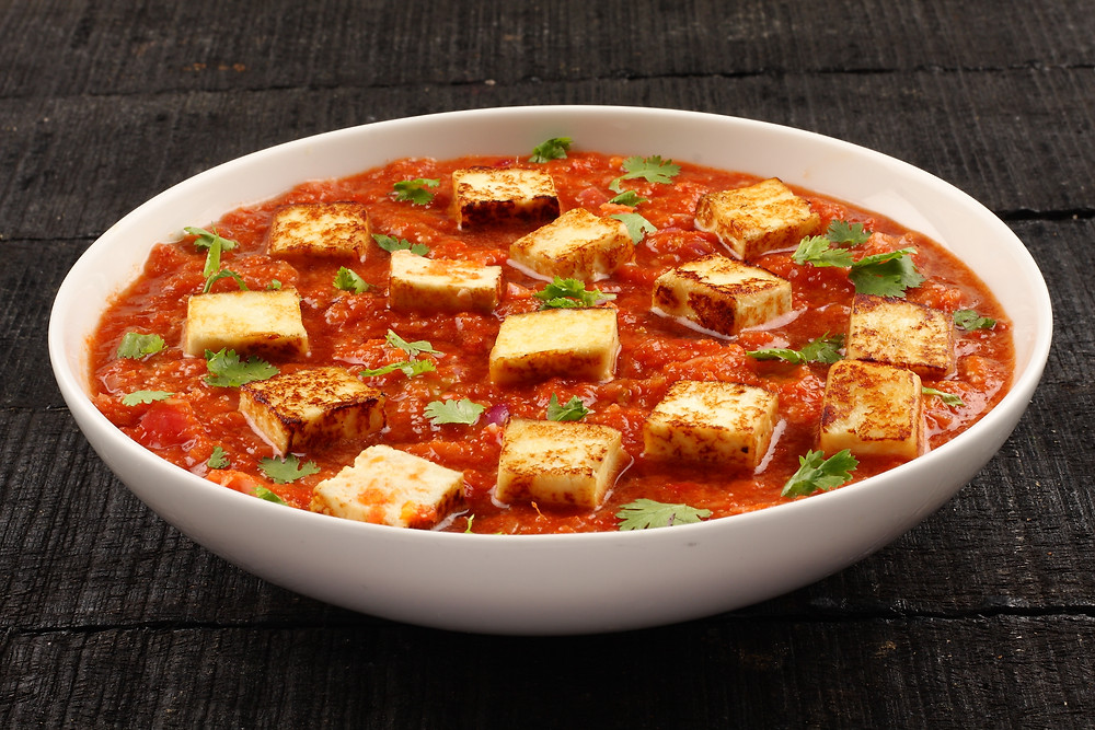 This is a picture of Tzamun, which is fried paneer cooked in a tomato sauce with green peppers.