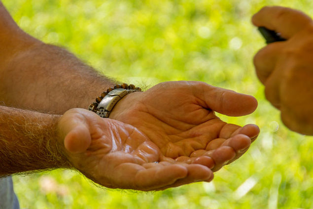man holding hands out awaiting a drop of oil