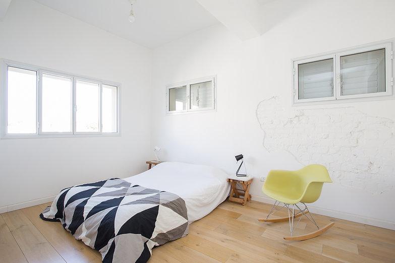 Chambre épurée et moderne avec parquet et murs blancs