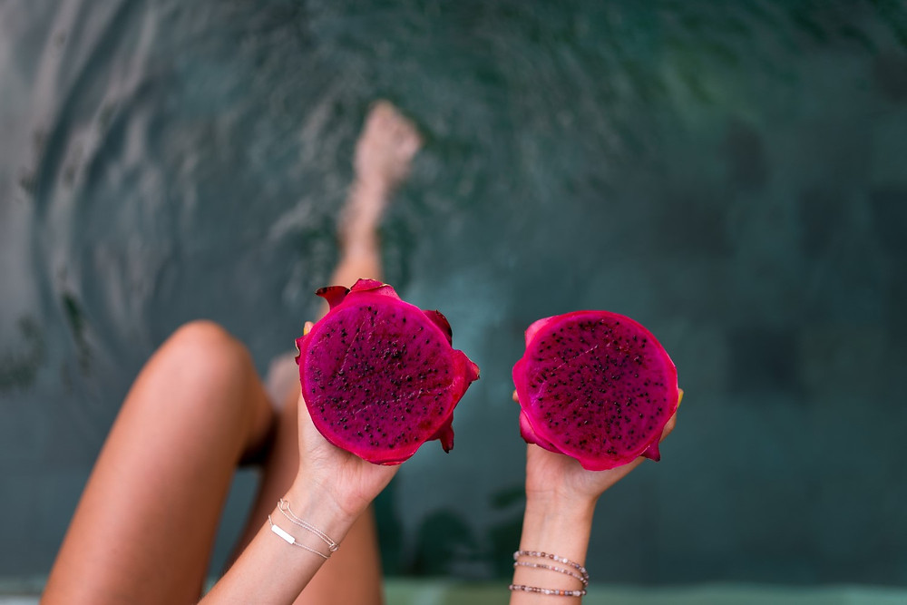 Woman With Foot In Water Holding Pink Pitaya or Dragon Fruit Cut Open