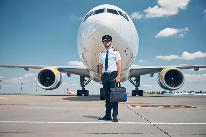 handsome-young-man-airline-worker-captain-hat-holding-travel-bag-smiling-while-standing-ai