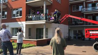 Mensen op straat kijken naar een hoogwerker, waarin 2 mensen naar een balkon op één hoog getakeld worden.