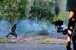 Dame in vechthouding met zwaard wordt gefilmd met rook op de achtergrond.