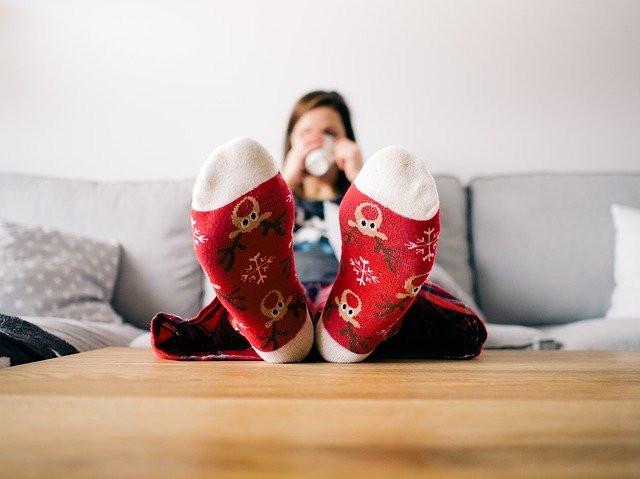 Vrouw met voeten op tafel, met wintersokken aan.