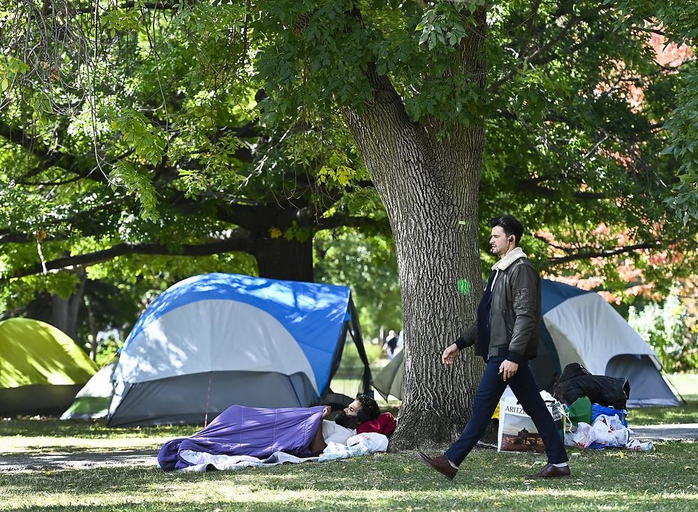 Una persona pasa junto a un sin techo mientras descansa al lado de las tiendas de campaña instaladas en el parque Trinity Bellwoods durante la pandemia COVID-19 en Toronto el lunes 21 de septiembre de 2020. LA PRENSA CANADIENSE/Nathan Denette