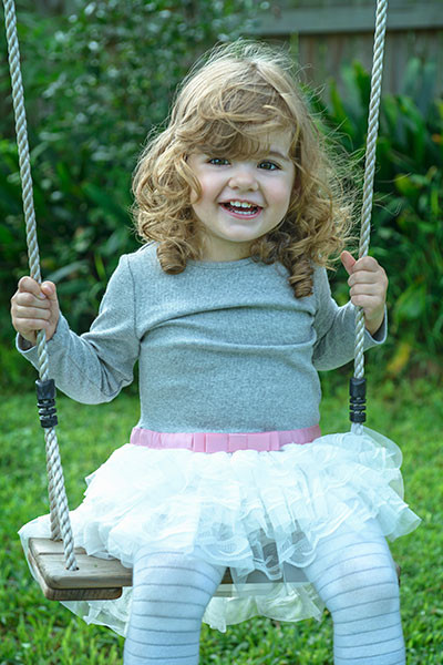 happy smiling little girl swinging on swing, photographer sydney carole diamond