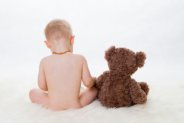 baby boy sitting with his back to the camera next to teddy bear, baby photography sydney