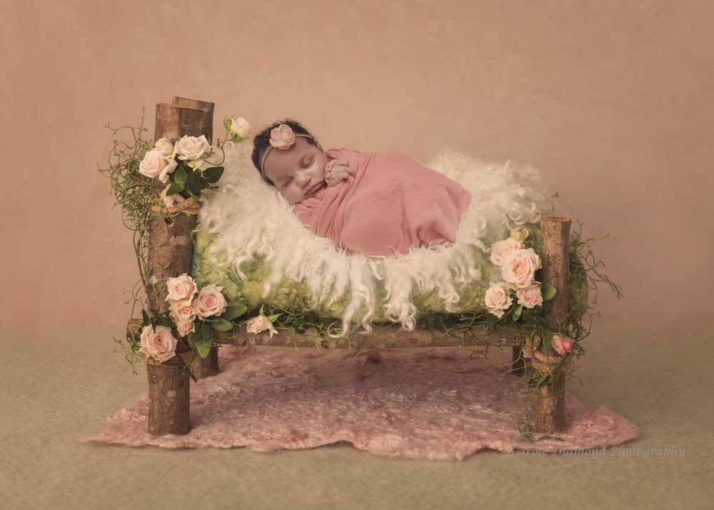 newborn baby sleeping on bed with flowers