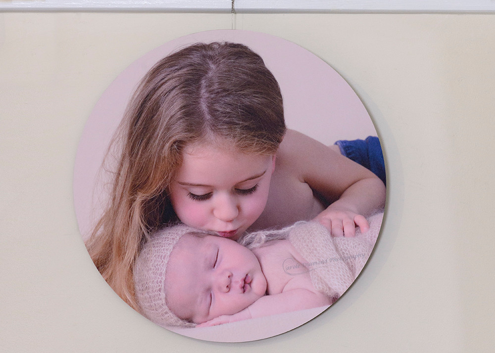 "20""x20"" wood round print of newborn baby with sister"