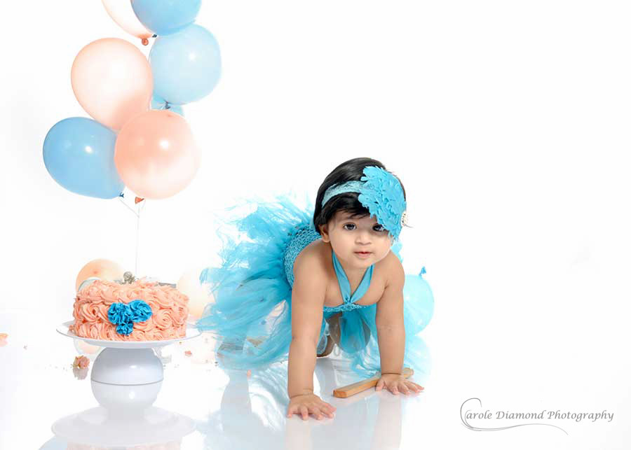 sweet girl in blue and apricot for her first birthday cake smash sydney