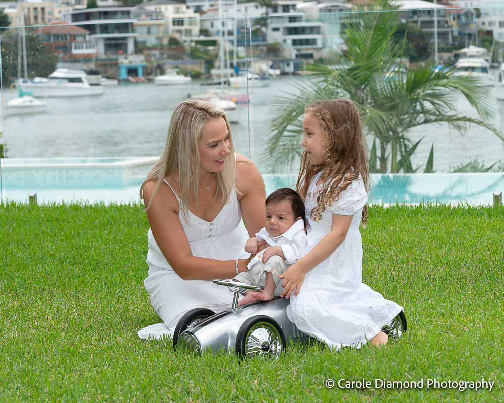Big sister miss 4 with mummy and newborn baby brother on toy ride on car in their gorgeous water front back yard, photographs taken by Carole Diamond Photography, Sutherland shire newborn photographer