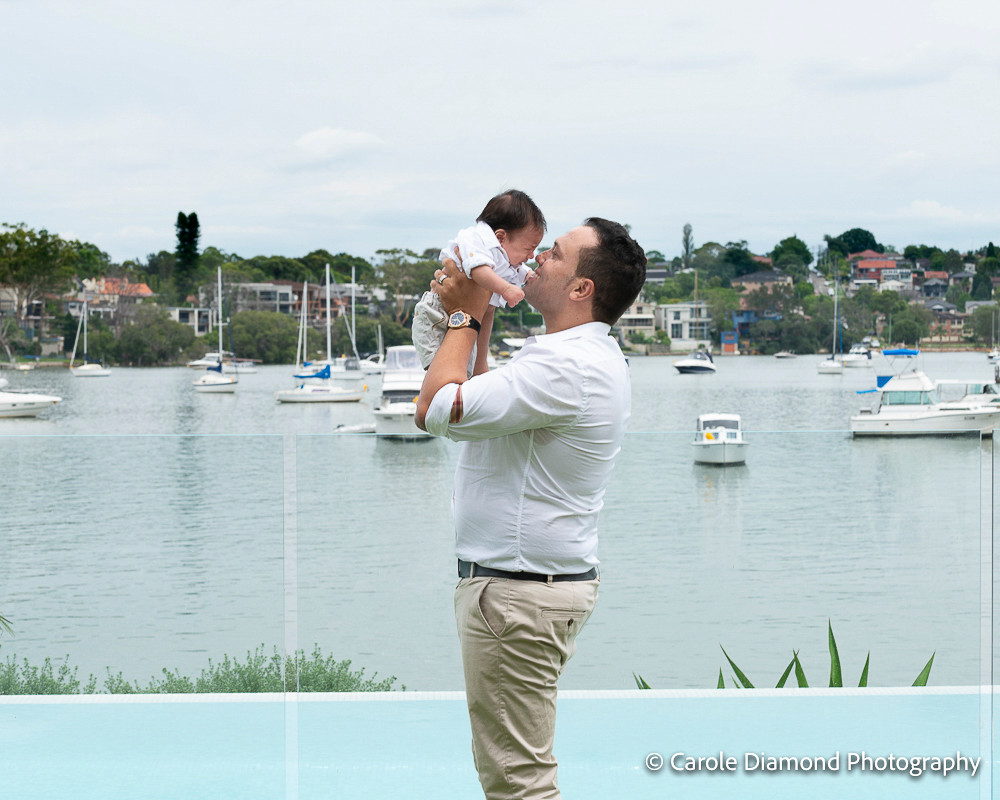 Wonderful Father of 3 with his newborn baby Malik in his back yard on the water. photographed by Sutherland shire family photographer Carole Diamond Photography