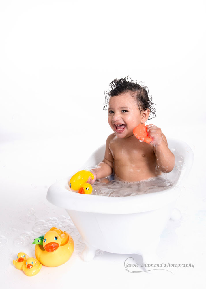 cheeky one year old in bath with toy duck and crab